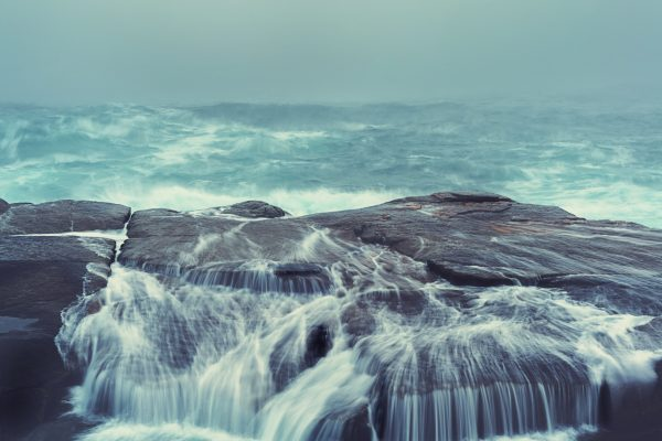 A wave washes over a narrow point of land.  Long exposure.